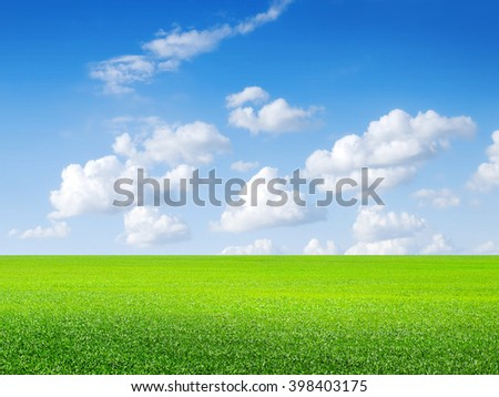 Green field, blue sky and white clouds. - stock photo