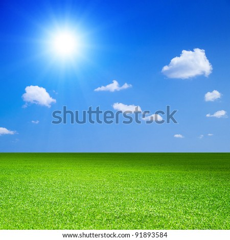 Green field, blue sky with white cloud and bright sun. - stock photo