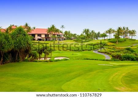 Green field for golf near hotel - stock photo