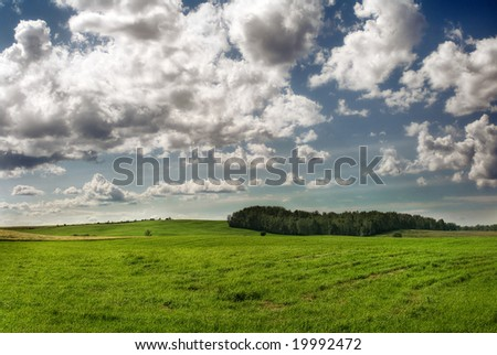 green field, forest and clouds - stock photo