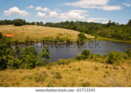 Green field, forest, lake and blue sky in national park, Thailand.