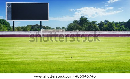 green field in stadium and blank scoreboard with trees and city in blue sky  - stock photo
