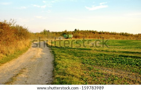 green field in the Czech Republic with tractor - stock photo
