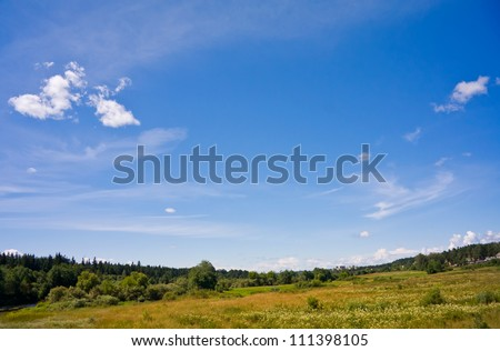 Green field landscape and blue sky with clouds - stock photo