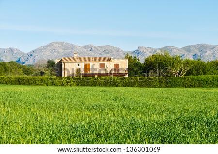 Green field rustic traditional house spring season, Majorca island, Spain - stock photo