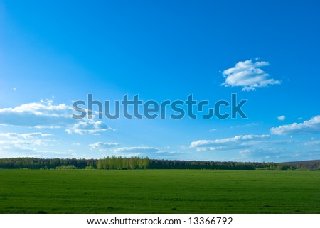 Green field under Blue sky with clouds - stock photo