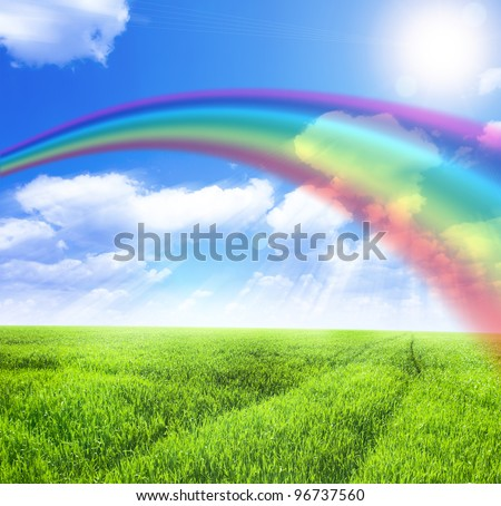 Green field under blue sky with sun and rainbow - stock photo