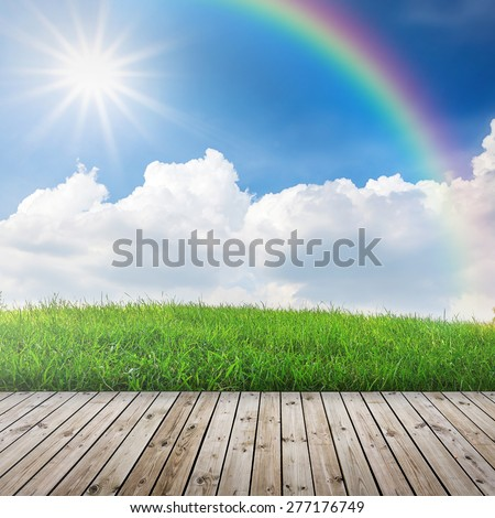 Green field under blue sky with sun beam. Wood floor - stock photo