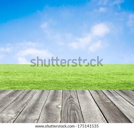Green field under blue sky. Wood planks floor. - stock photo