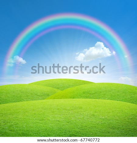 Green field with blue sky and perfect rainbow - stock photo
