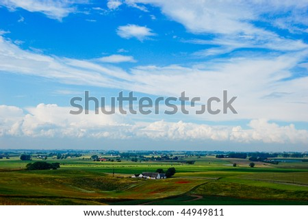 Green field with house on sunny day - stock photo