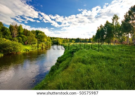 Green field with river under blue sky - stock photo