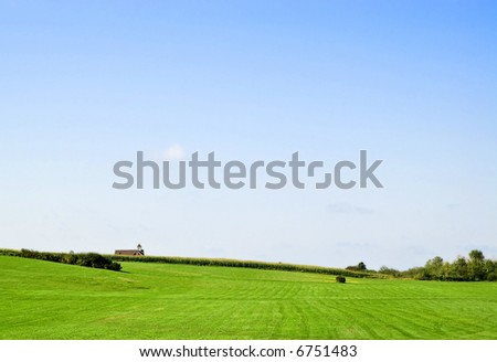 Green field with school-house in distance (Grand Pre, Nova Scotia) - stock photo