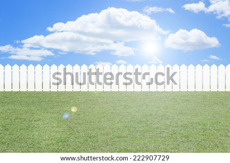Green field with white fence and blue sky and clouds - stock photo