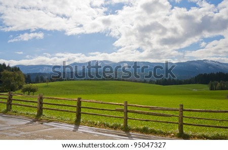 Green field with wooden fence and mountain landscape in Bavarian Alps, Germany