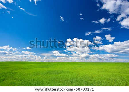 green filed under blue skies with white clouds - stock photo