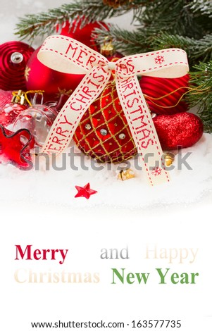 green fir tree and red christmas decorations  on white snow with copy space