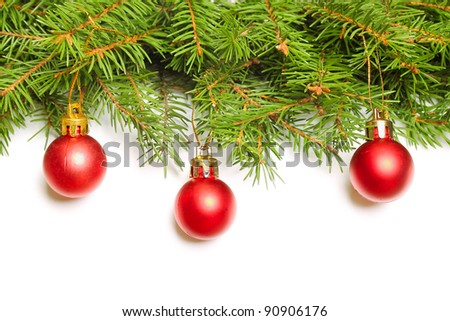 Green fir tree branch with Christmas baubles on white background - stock photo