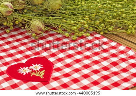 Green flax twigs  with  linen seeds on checkered red white tablecloth  heart appliques background - stock photo