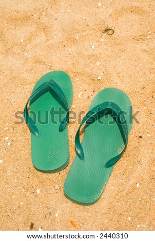 Green flip-flops on a sandy beach
