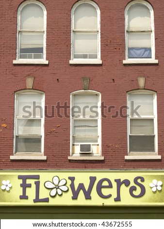 Green flower shop sign underneath six windows on a red brick building. Ontario, Canada. - stock photo