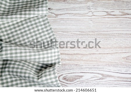 Green folded tablecloth on wooden table  - stock photo