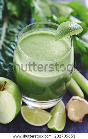 Green food :juiced health juice in glass surrounded by cut up lime, ginger, apple, celery and spinach - stock photo