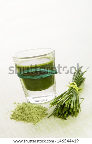 Green food supplement. Spirulina, chlorella and wheatgrass. Green drink, wheatgrass blades and ground powder isolated on white background. Healthy lifestyle. - stock photo