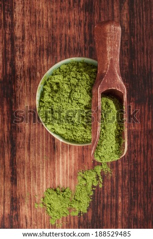 Green food supplement. Wheatgrass ground on brown wooden scoop and round bowl on brown wooden background, top view. Healthy natural detox.  - stock photo