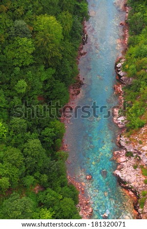 Green forest and turquoise stream of water flowing at the bottom of a canyon - stock photo