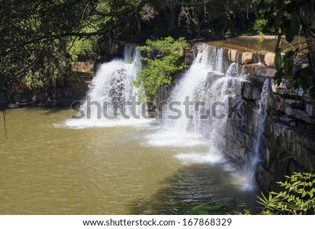 green forest with waterfall - stock photo