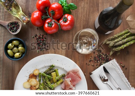 Green fresh and fried asparagus with ham, potatos, tomatoes, wine. - stock photo