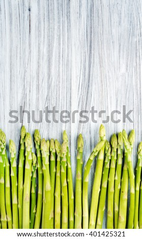 Green fresh asparagus on light painted wooden background. Top view, copy space, vertical - stock photo