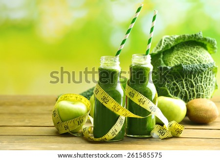 Green fresh healthy juice in glass bottles with fruits and vegetables on wooden table and bright background - stock photo