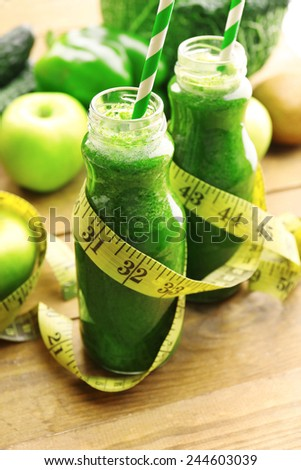 Green fresh healthy juice in glass bottles with fruits and vegetables on wooden table background - stock photo