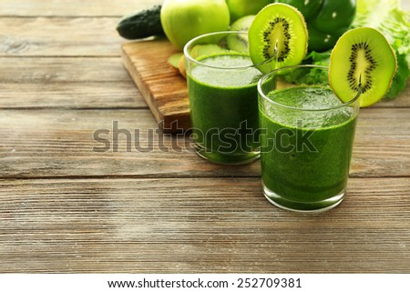 Green fresh healthy juice with fruits and vegetables on cutting board and wooden table background - stock photo