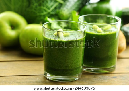 Green fresh healthy juice with fruits and vegetables on wooden table background - stock photo
