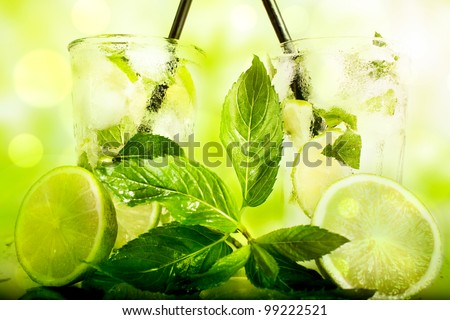 Green fresh Mojito cocktail with macro mint in foreground; textured spring cocktail background - stock photo