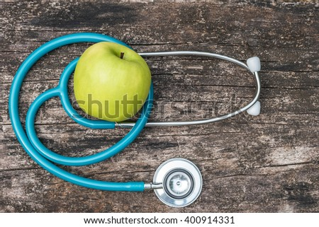 Green fresh organic natural nutrient apple with doctor's stethoscope heart shape on grunge old aged wood background: World health day WHD April 7 symbolic conceptual design idea for healthy fruit food - stock photo
