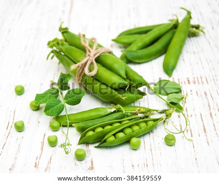 Green fresh peas on a wooden background - stock photo