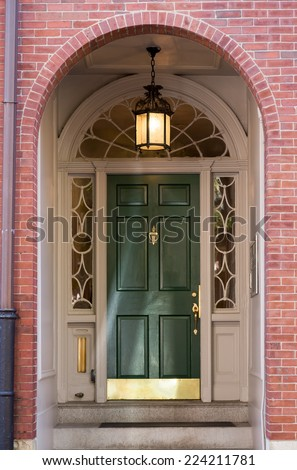 Green Front Door with White Ornate Archway Door Frame in Brick Building - stock photo