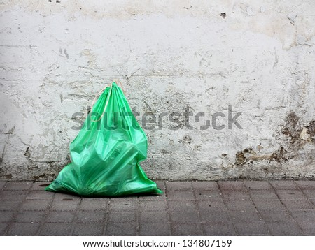 Green garbage bag on street - stock photo