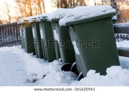 Green garbage cans in a row with snow on top on cold winter day with orange sunlight in background - stock photo