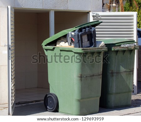 Green garbage cans on  the sidewalk - stock photo