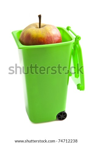Green garbage container with apple isolated over white - stock photo