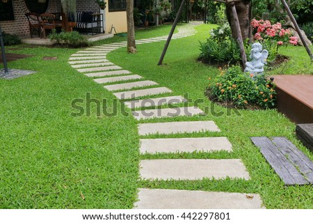 green garden, Landscaping in the garden. The path in the garden.pathway in the park,curve walkway with stone tile on green grass field and flower garden.yard with table and chair set.