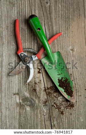Green garden spade and scissors with ground on old wooden desk