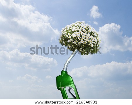 Green gas pump with blooming plant at end of nozzle - stock photo
