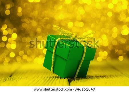 Green gift box against yellow defocused lights - stock photo