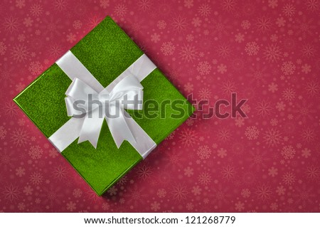 Green gift box with white ribbon on red background - stock photo